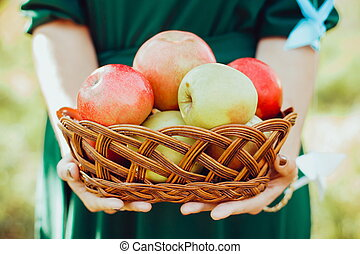the man is holding a basket with red apples