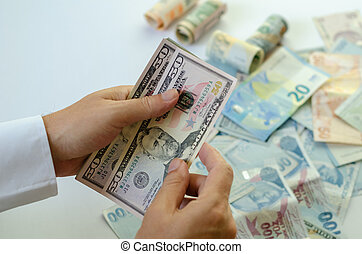 The man is holding banknotes in his hands.