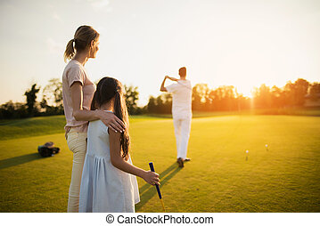 The man is looking into the distance, he just hit the ball with the club, the woman and the girl are looking at him