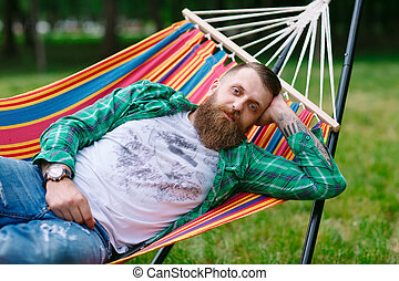 The man is lying on a hammock.