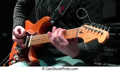 The man is masterly playing the electric guitar on a black background. close-up. In slow motion.