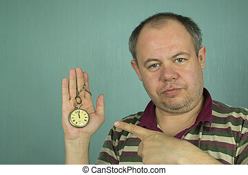the man is pointing at the clock