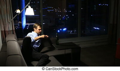 Drunk man drinking beer by window at home at night
