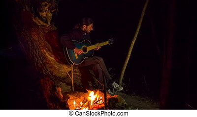 the man is sitting near the fire and playing the guitar