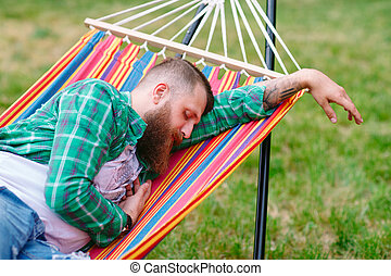 The man is sleeping on a hammock.
