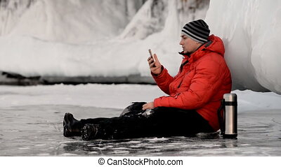 The man is using the smartphone by the ice rock.