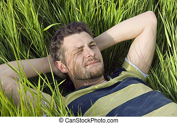 The man lies on a grass