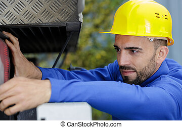 the man looks at the lorry in the pit
