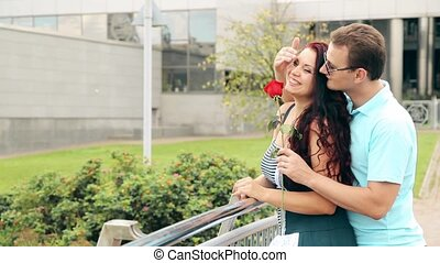 The man made a surprise to a beautiful girl by giving her a flower, a red rose