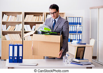 The man moving office with box and his belongings