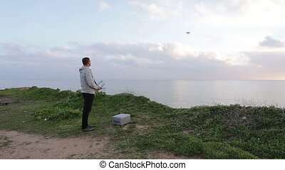 The man on the shore of a remote control for drone takes...