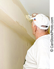 The man paints a withe wall