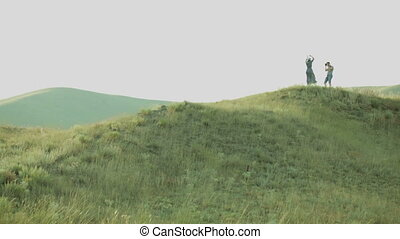 the man photographs the girl on a hill in a hat