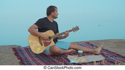 The Man playing the guitar and singing on the beach.