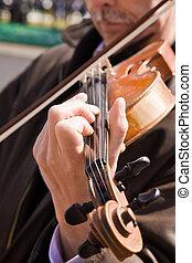 The man plays a violin.