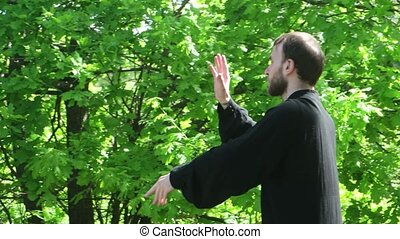 the guy practices Wushu tai Chi in nature in the forest