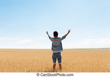 the man raised his hands to the sky, against the background of a wheat field, the guy in the cap and shirt, crying to God for help