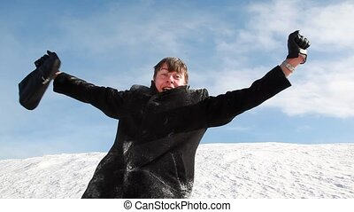 The man rejoices against the snow slope - The man in dark...