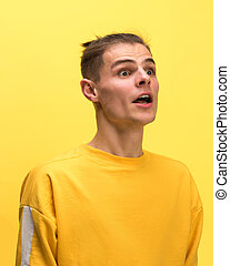 The man screaming with open mouth isolated on yellow background, concept face emotion