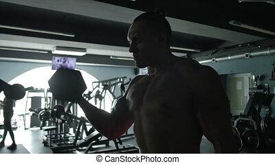 The man shakes his biceps.