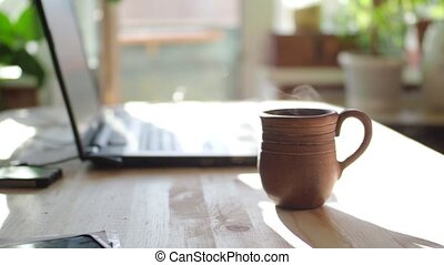 the man sits down at the table and starts typing on the keyboard. In the foreground a mug of hot tea. Focus on the mug.
