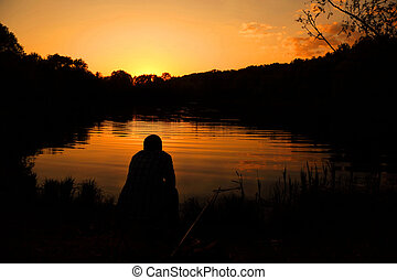 The man sits with a fishing tackle and fishes on the bank of lake, during a decline.