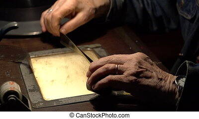 The man sitting at the editing table holds a film in his hands.