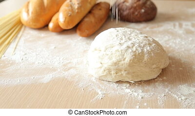 the man sprinkles the dough with flour