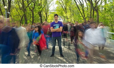 The man stand in the ghost-like crowd flow, on background green trees . Time lapse