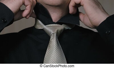 The man straightens the knot of his tie. Businessman going...
