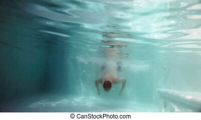 The man swims under water in the pool