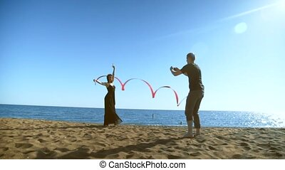 The man takes pictures on the phone. Woman in a black long dress with a red gymnastic ribbon poses.