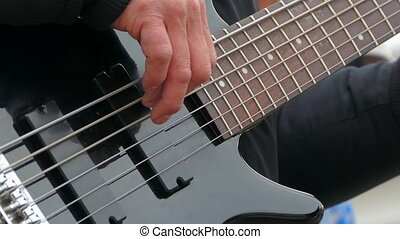 The man takes the chords with his fingertips on the strings of an electric guitar