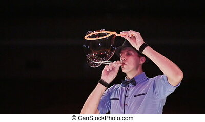 The man the actor blows balls on a soap bubble and twirls blowing on him. Soap bubbles show.