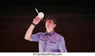 The man the actor blows two soap bubbles with a gray smoke and plays with them in tennis.