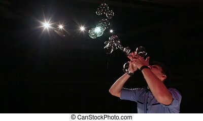 The man the actor fingers of hands blows soap bubbles. Soap bubbles show.
