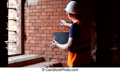 The man the historian examines the walls of the old building, checks the density of the brick, preparation for reconstruction