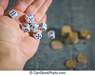 The man throws the game dice on the table with coins. Money and game cubes.