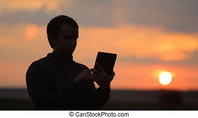 The man touches the tablet. Beautiful sunset on the background