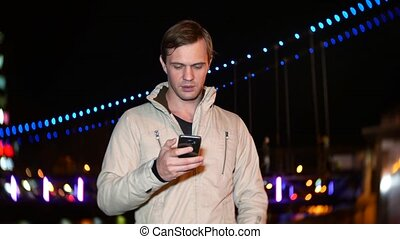 The man uses his smartphone with a touch screen. on a night...