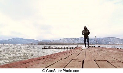 The man walks on the pier - Sad pensive man walks on the...