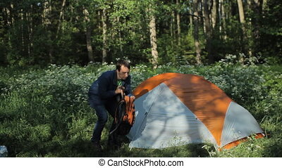The man wears a backpack near tent. Early morning in the forest