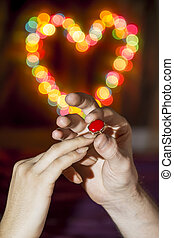 The man wears a woman's finger ring against the backdrop of a colorful heart-shaped bokeh