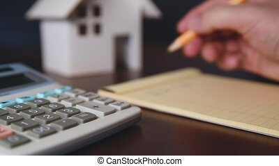calculating the cost of buying a house - The man who is...