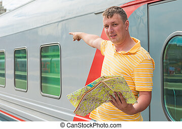 the man with a map shows the direction of the train station