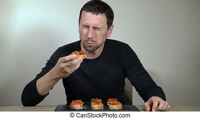 The man with an appetite eats bruschetta at home