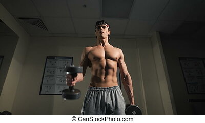 The man with dumbbells in sports club