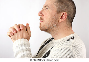 the man with folded hands in prayer looking up
