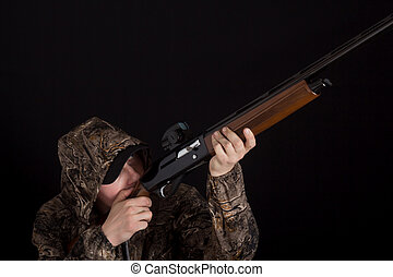 The man with the gun aims. Hunter in camouflage clothes with a shotgun on a black background. Military with weapons. Copy space. Preparation for spring or autumn hunting.
