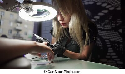 The manicurist makes pedicure procedure of recovery and nail...